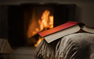 Peceful image of open book resting on a arm rest of a couch. Warm fireplace on background.