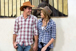 loving american western couple holding hands in stable