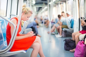 Beautiful blonde caucasian lady in red dress traveling by metro.