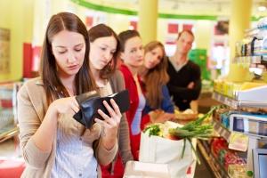Frau sucht ihr Geld zusammen an der Supermarktkasse