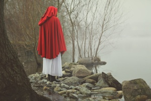 Little red riding hood on a shore of a misty lake . Sadness and surreal concept
