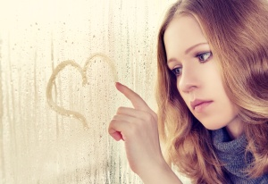 sad enamored girl draws a heart on the window in the rain
